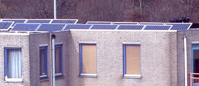 PV-system of 10 solar panels (1020 Wp), 6 on front row and 4 on back row on flat roof above 4th floor (telephoto)